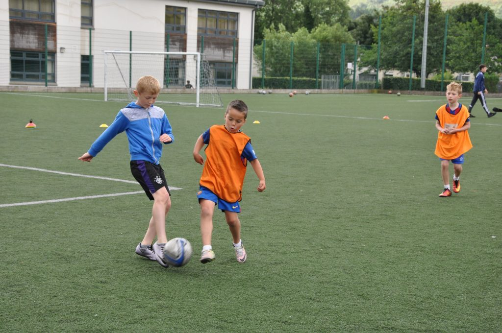 Young footballers practise their tackling skills.