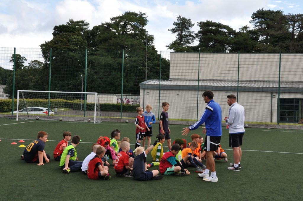Coaches Graham Muir and Christopher Monk explain a manoeuvre before children try it out themselves.
