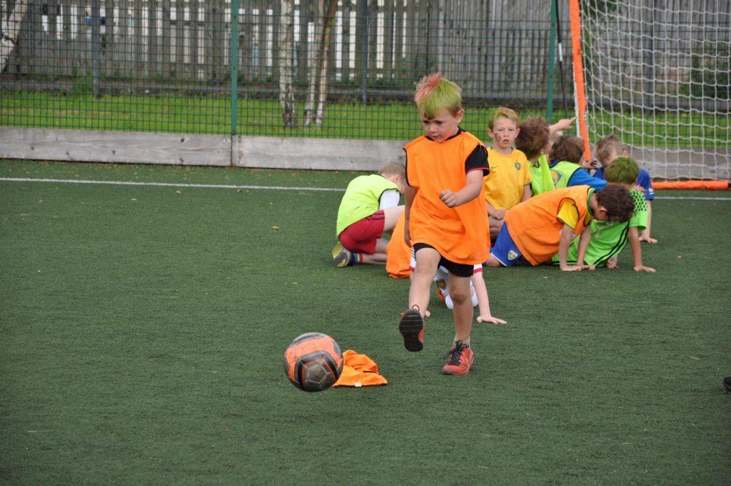 A young footballer practices his ball control and accuracy.