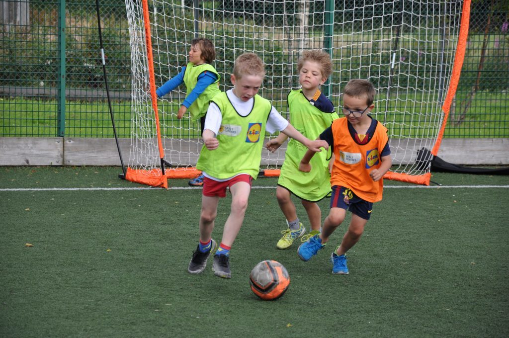 Eyes on the ball, children take part in a mini match.