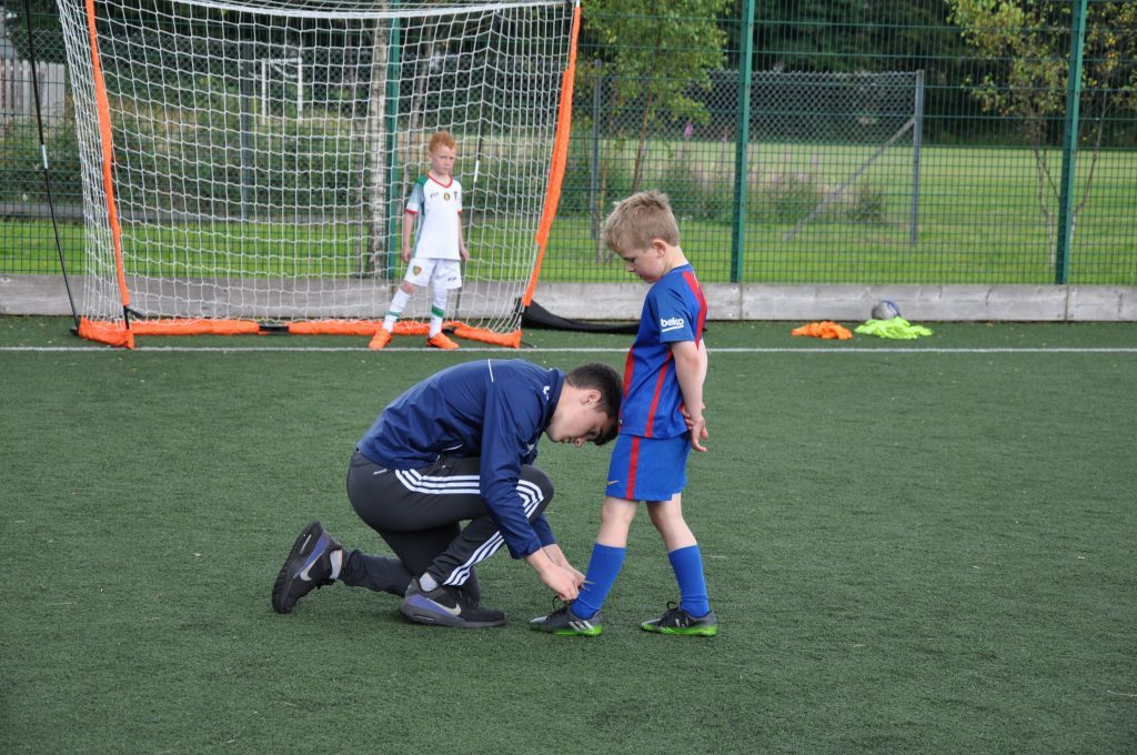 Assistant coach David Copperwheat ensures that a youngster does not trip over his laces.