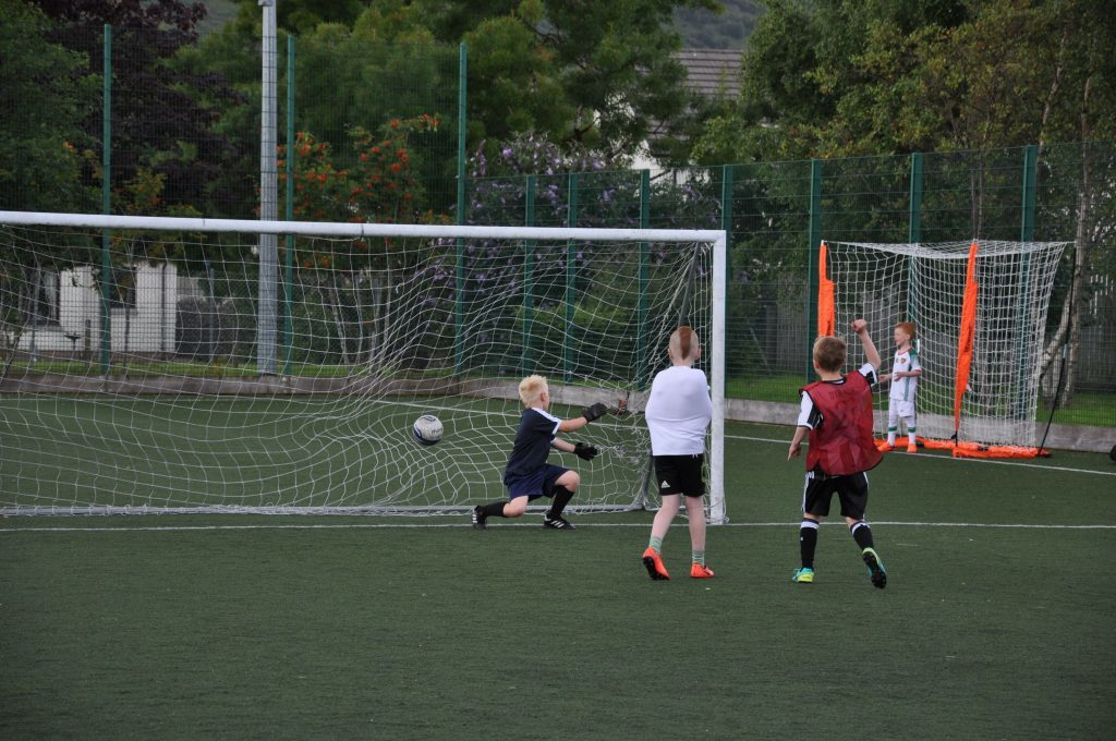 Goal! A young player sneaks one past the goalkeeper.