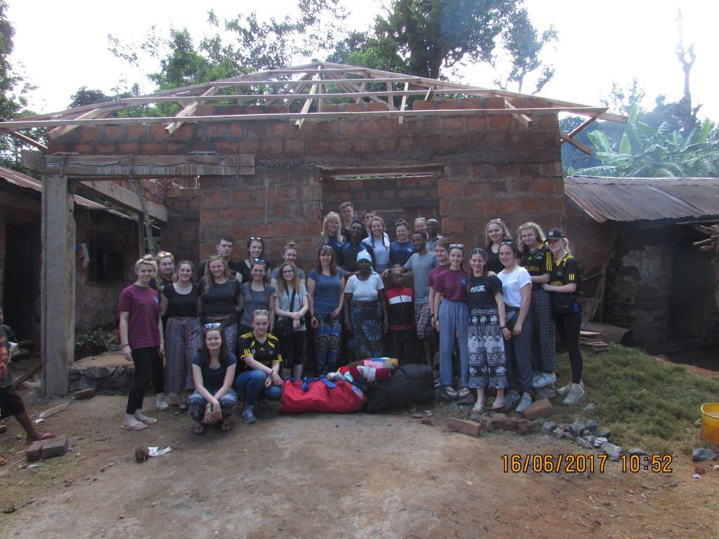 A final day group photo at Mama Eliambuya's home showing the work the group completed.