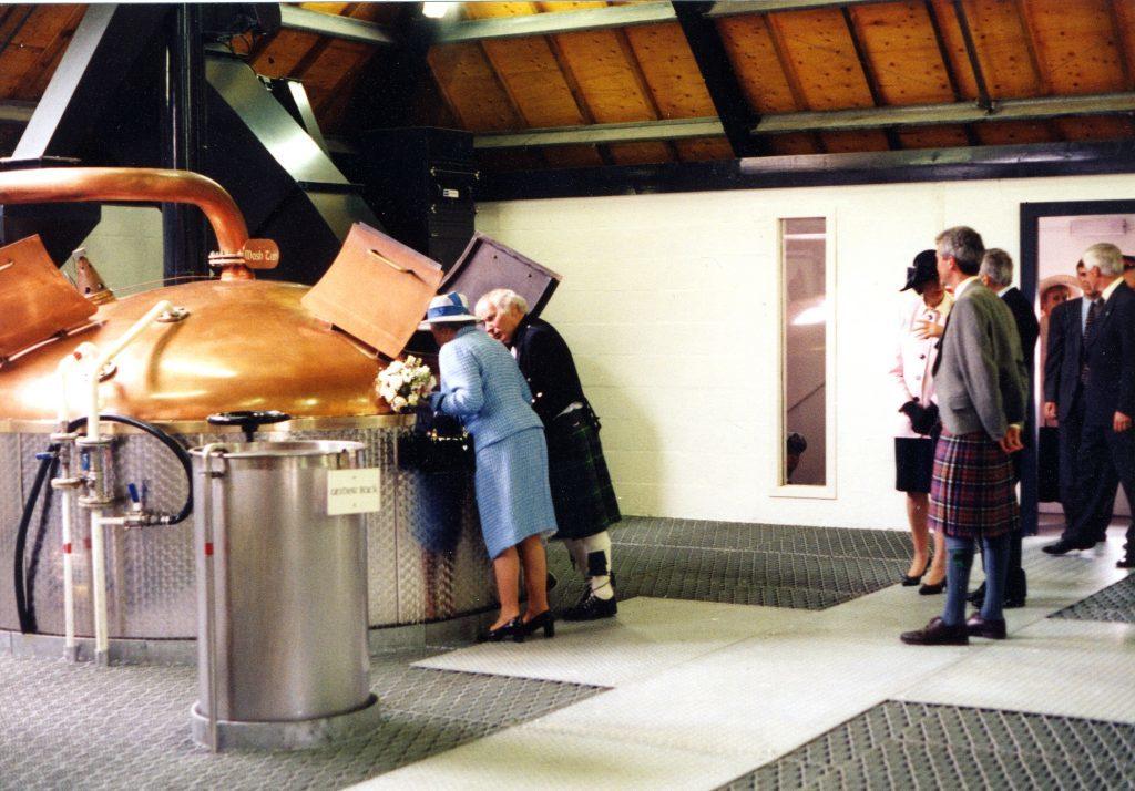 The Queen and distiller Gordon Mitchell peer into a mash tun at the Lochranza Distillery.