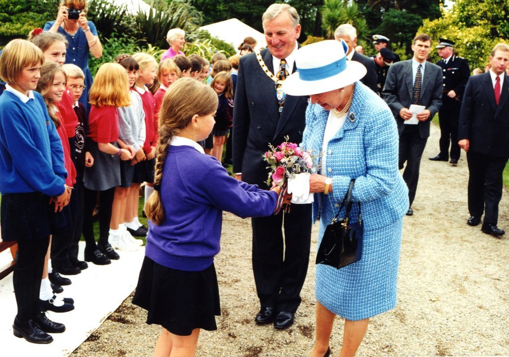Nine year old Joanne McLellan presents The Queen with a posy.