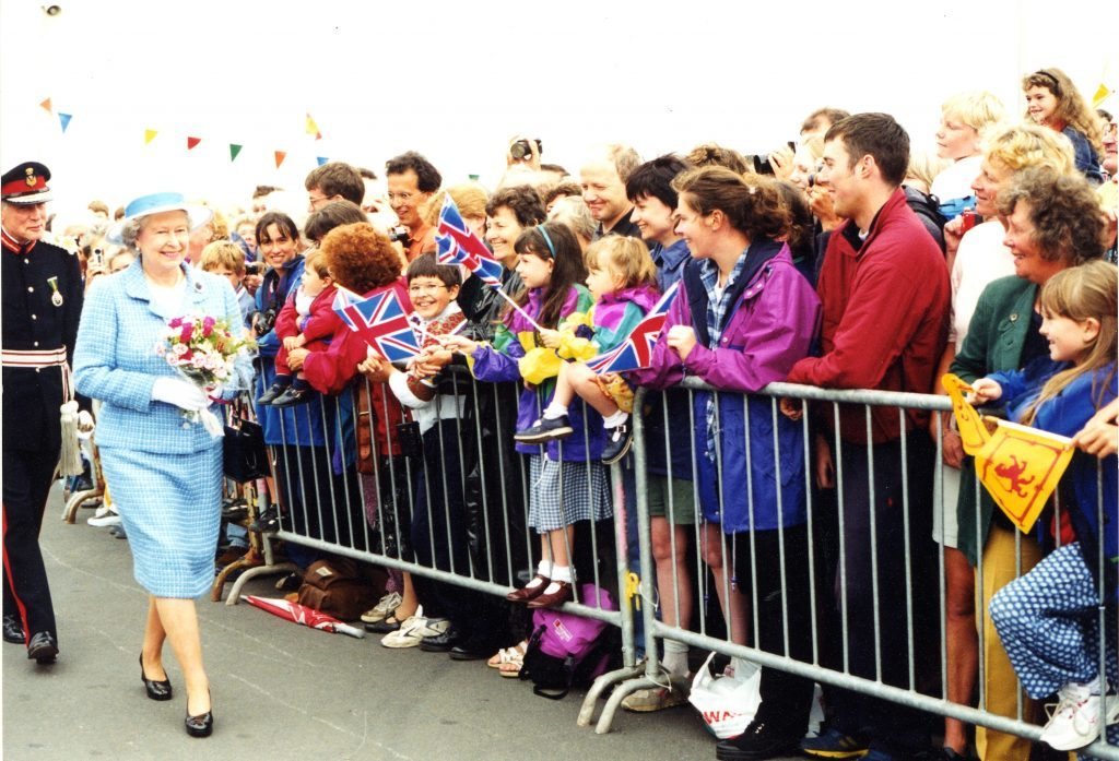The Queen is adored by the crowds gathered at the pier.