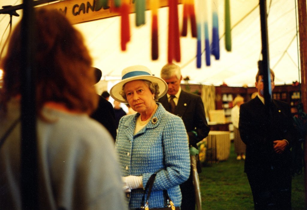 The Queen listens intently to the story of candle making.
