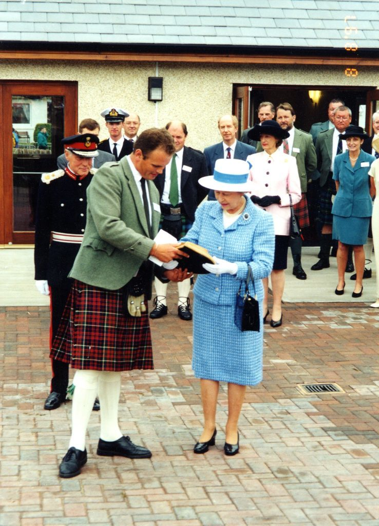 The Queen receives a Marvin Elliot carving given to her by Alastair Dobson.