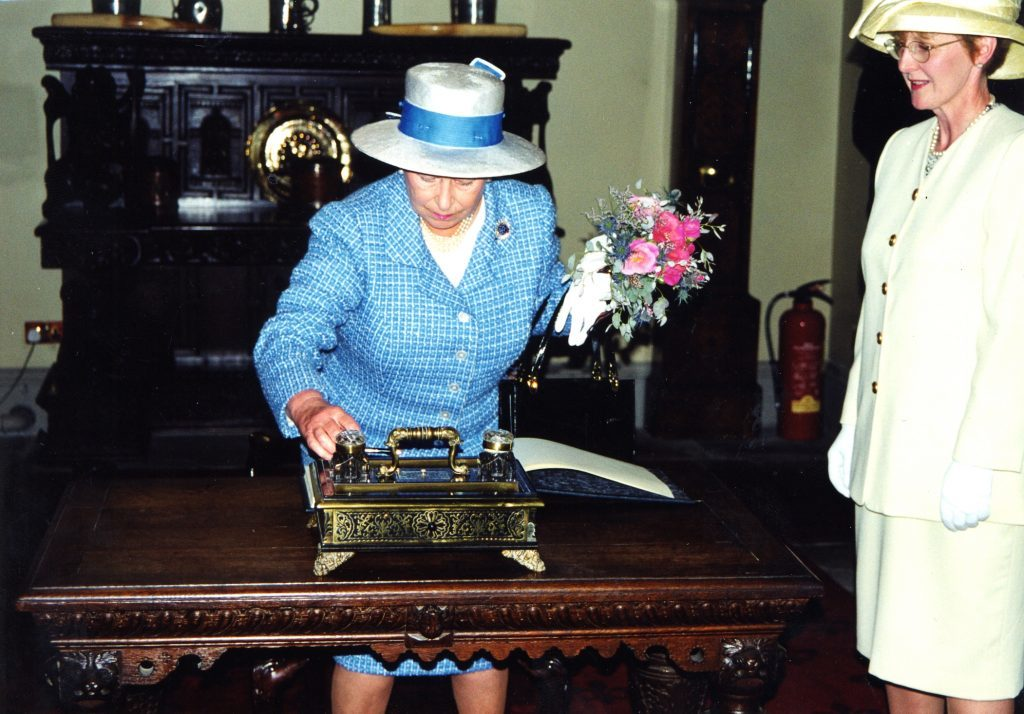 The Queen signs the visitors book with NTS administrator Veronica Woodman.