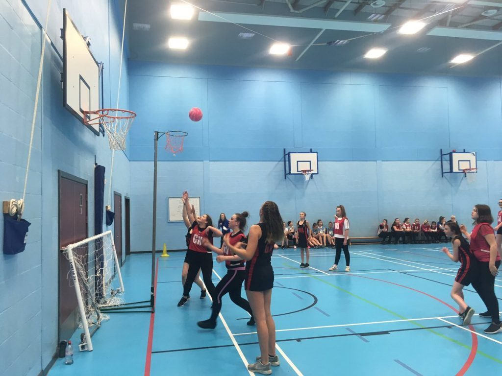 An Arran player watches on as an opposition player throws the ball towards the net