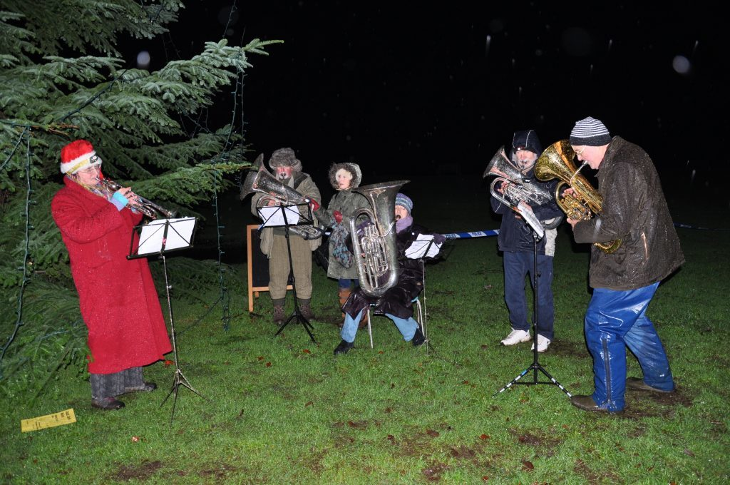 ​Members of the Arran Brass Band brave the driving rain to perform at the Christmas tree lighting ceremony. 01_B48sparkle12