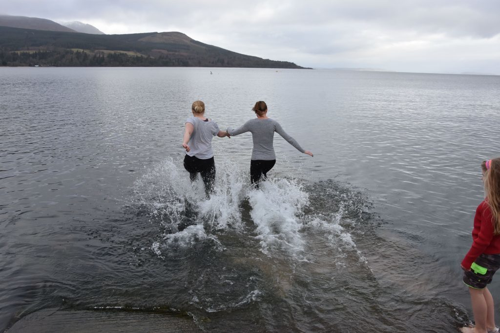 Two ladies rush into the water amid screams and giggles