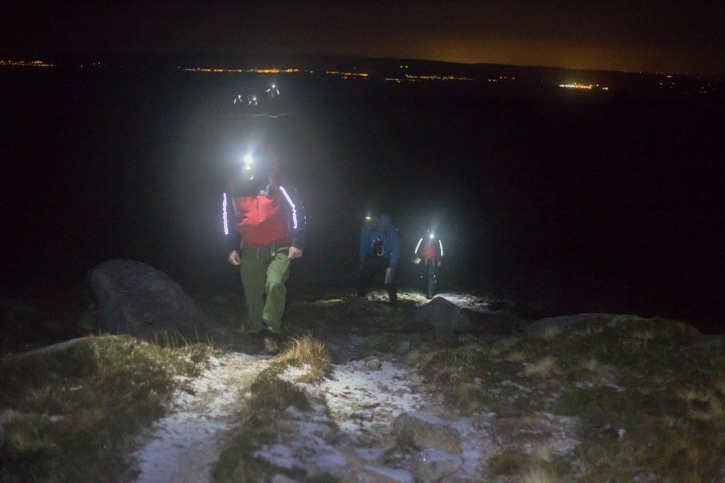 Arran Mountain Rescue Team members navigate up the mountain with the mainland lights visible behind them