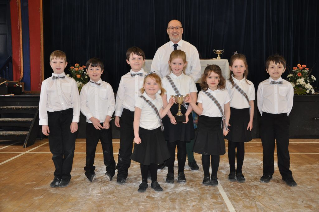Shiskine Primary and adjudicator Eric Findlay with the Corrie Scottish Country Dancing Cup