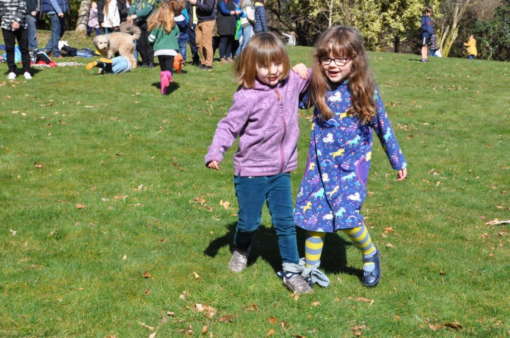 Two young girls have a laugh during the three-legged race