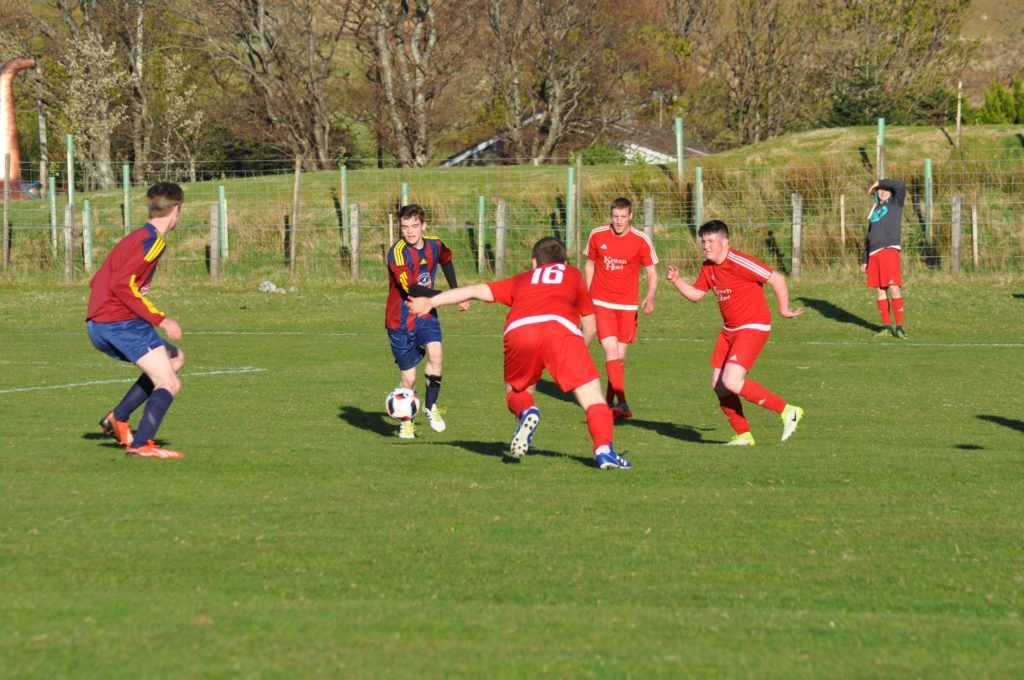 Players scramble for the ball positioned uncomfortably close to the Northend goal .