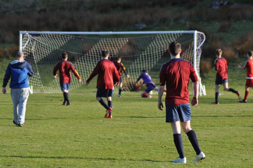 A row of Northend players watch as their team mate places the ball in the back of the net.