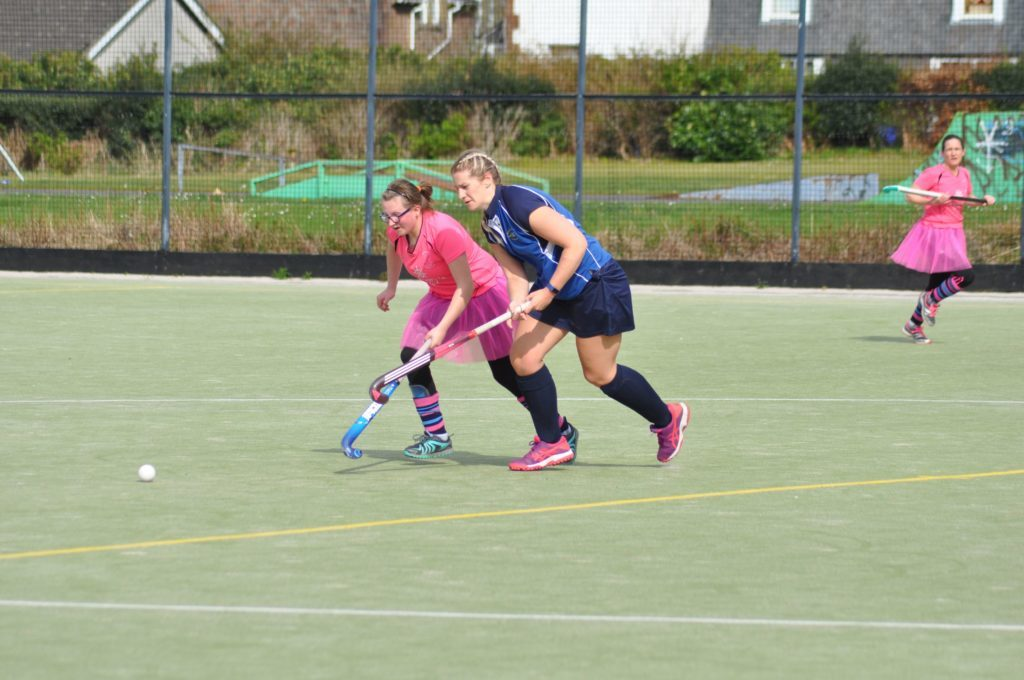 Mia Walker and a Stirling player run to claim possession of the ball.