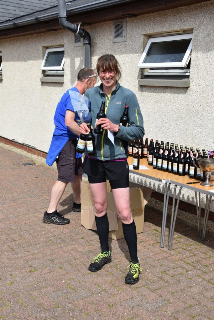 First local female Corinna Goeckeritz receives her medal and the traditional prize of beer.