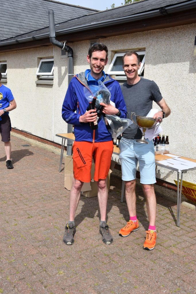 First local male runner, Malcolm Wilkinson receives his medal and traditional beers from race organiser Peter Mackie.