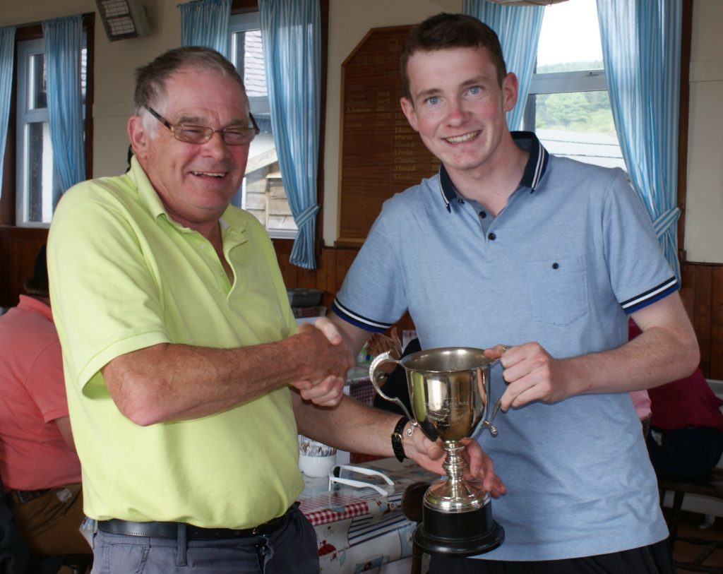 Ross Traill, winner of the Duncan Sillars Memorial Trophy at Machrie Bay Golf Club, receives the award from Brian Sherwood.