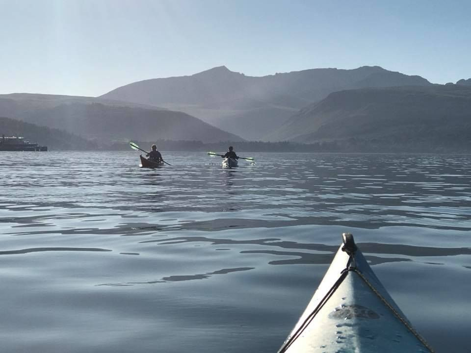 Paddlers in Brodick are silhouetted by the mountains of Glen Rosa in the early evening gloaming.