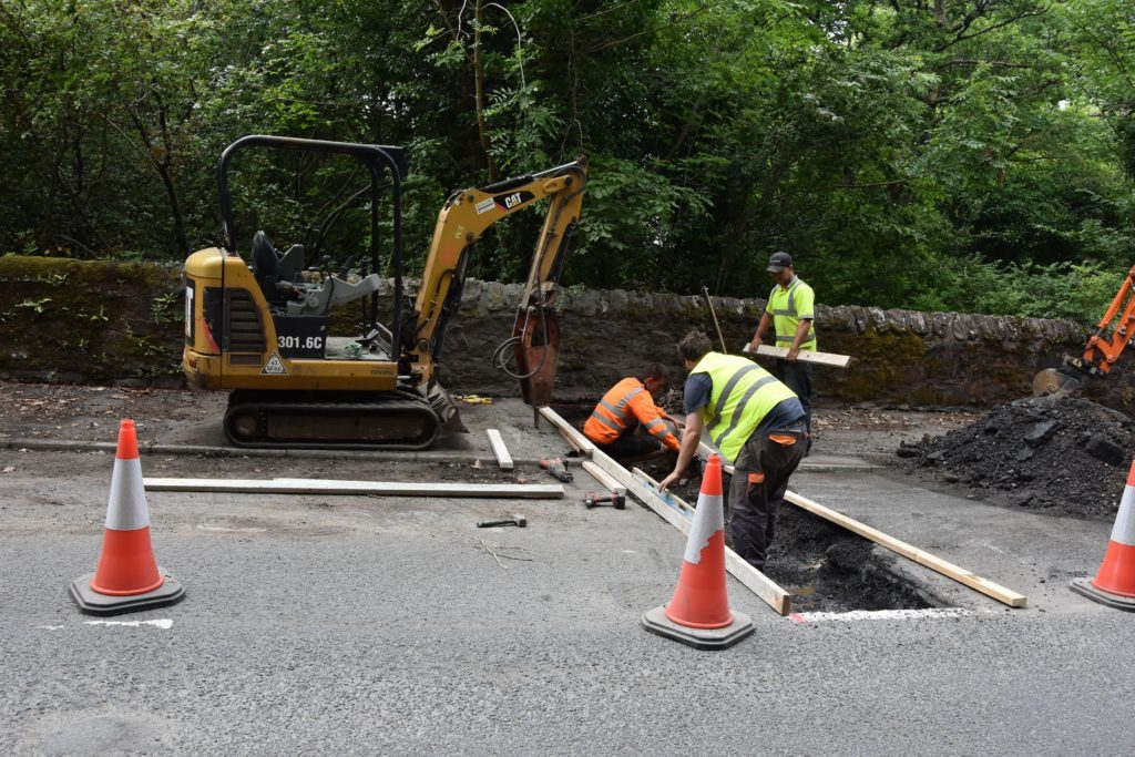 Workmen begin work on the road and pavement to strengthen the abutment.