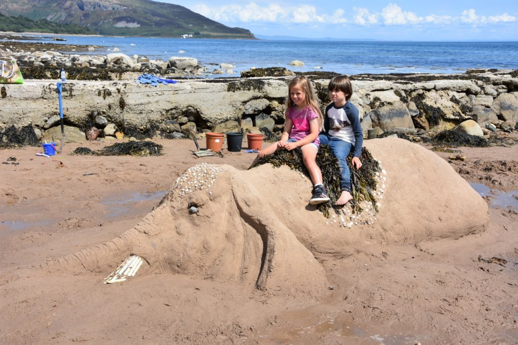 Unable to resist, children go for an imaginary elephant safari on Whiting Bay beach.