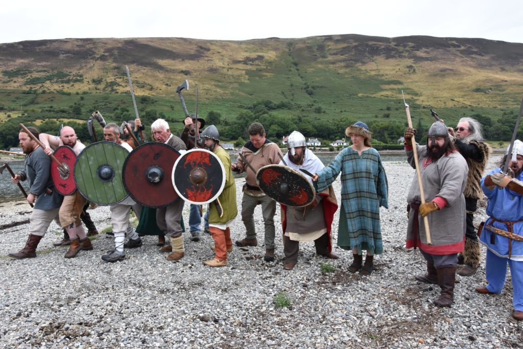 Attacking Vikings march onto the shore with their weapons elevated.