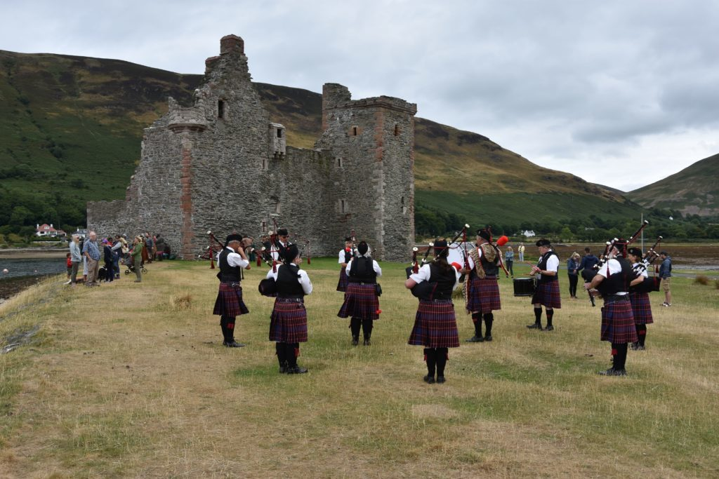 The Arran Pipe Band perform with Lochranza Castle as a dramatic backdrop.