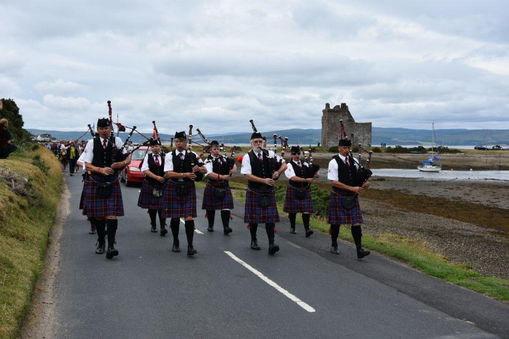 Leading the parade, the Arran Pipe Band with Lochranza Castle behind them.