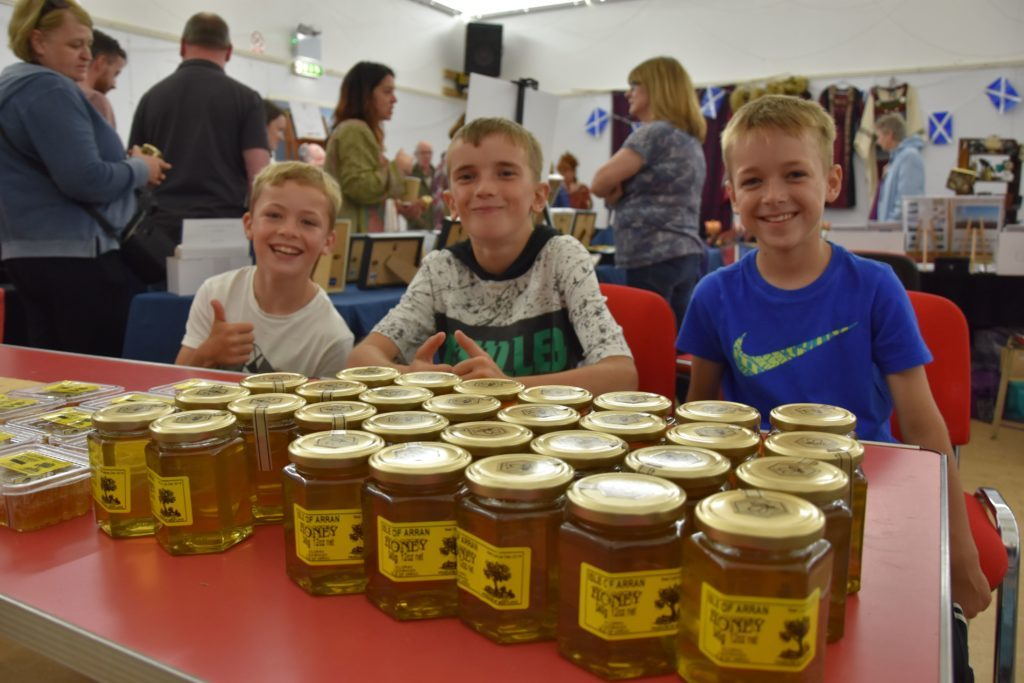 Sweet smiling faces, Fergus West, Ewan Morrison and Scott O Neill host a honey stall in the village hall.