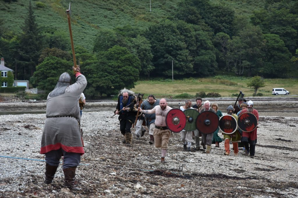 A Celtic warrior defends against a Viking attack during the Viking re-enactment on the cobbled beach.