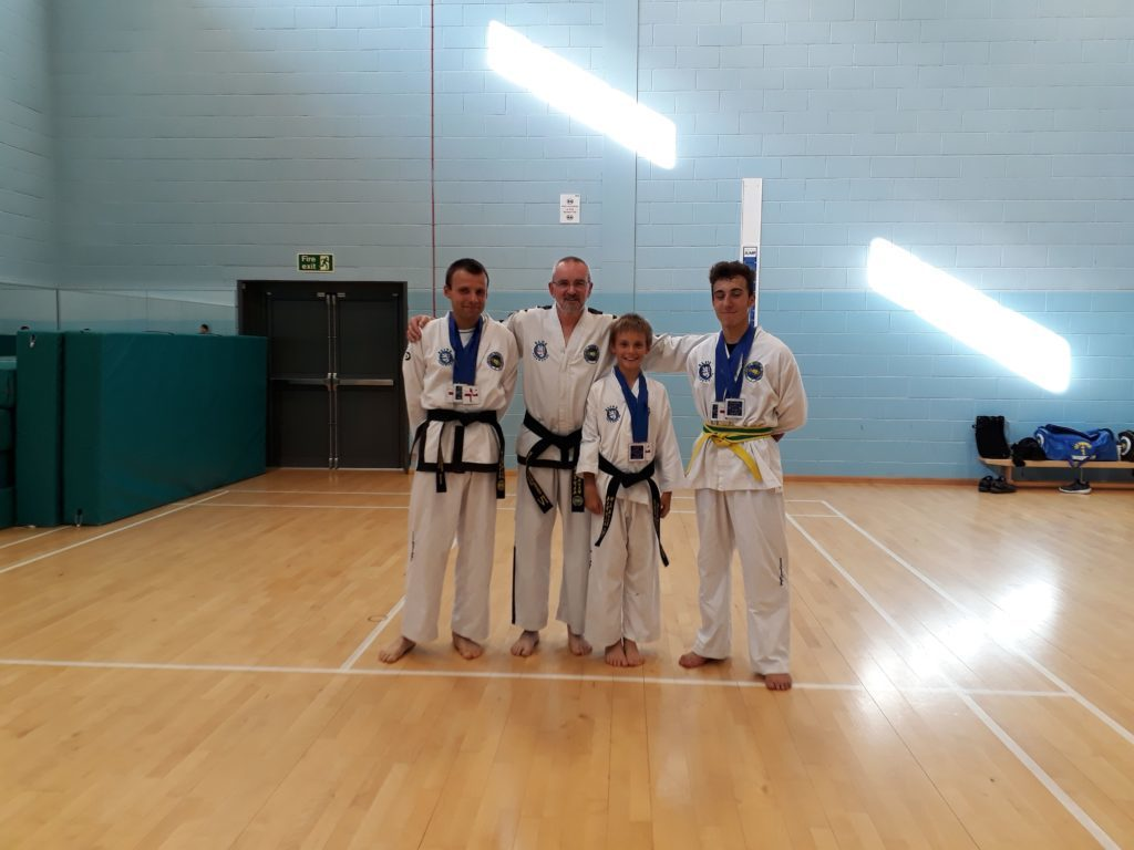 Proud instructor John Divine with his three champion students.