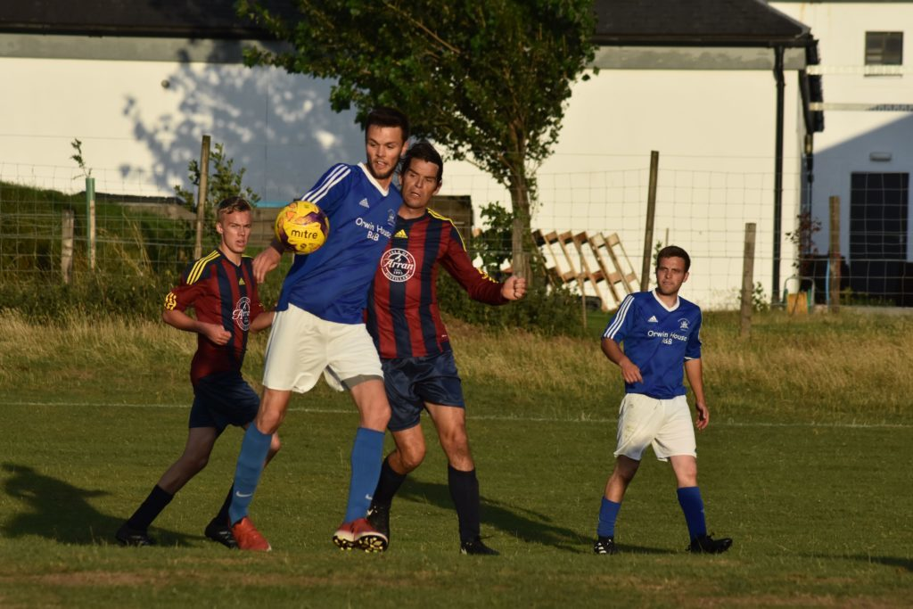 Goal scorer for Northend, Andy McNamara challenges Brodick's Matthew Dobson for possession.