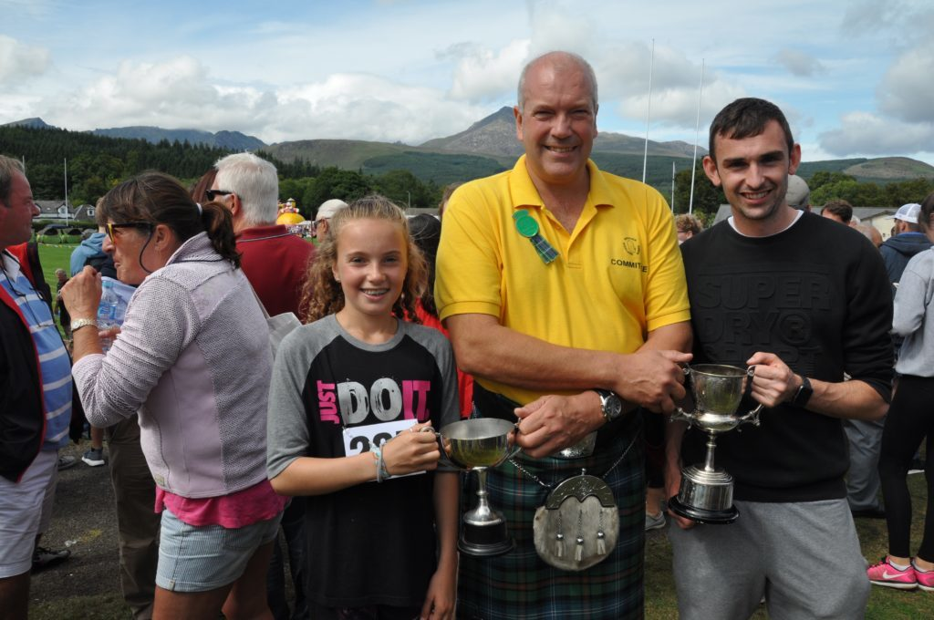 Chairman Donald MacKelvie presents Archie McNicol and his daughter Isla with the 100m trophies.