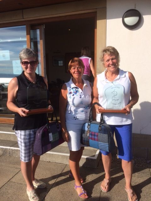 Lady convenor Clare Buchanan presents Shiskine Golf Club open winners, Ann Lang and Elspeth Inch, with their prizes.