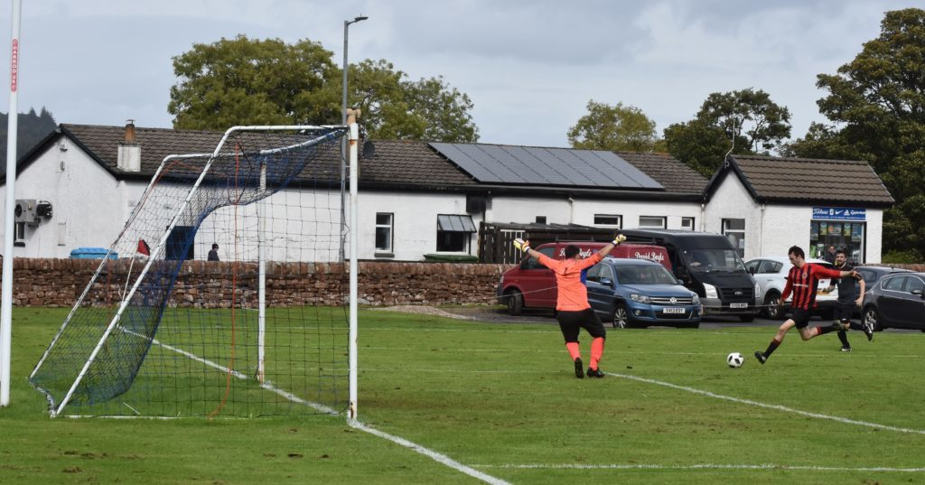 Archie McNicol powers towards goal to score for Arran.