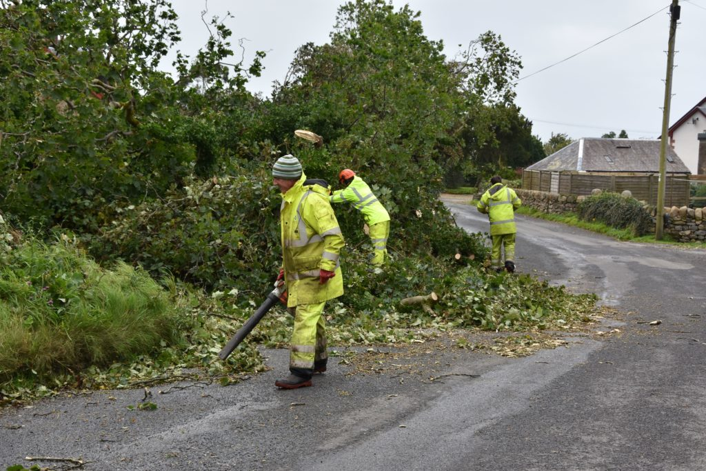 Workmen use chainsaws and electric blowers to clear the road in Shiskine.