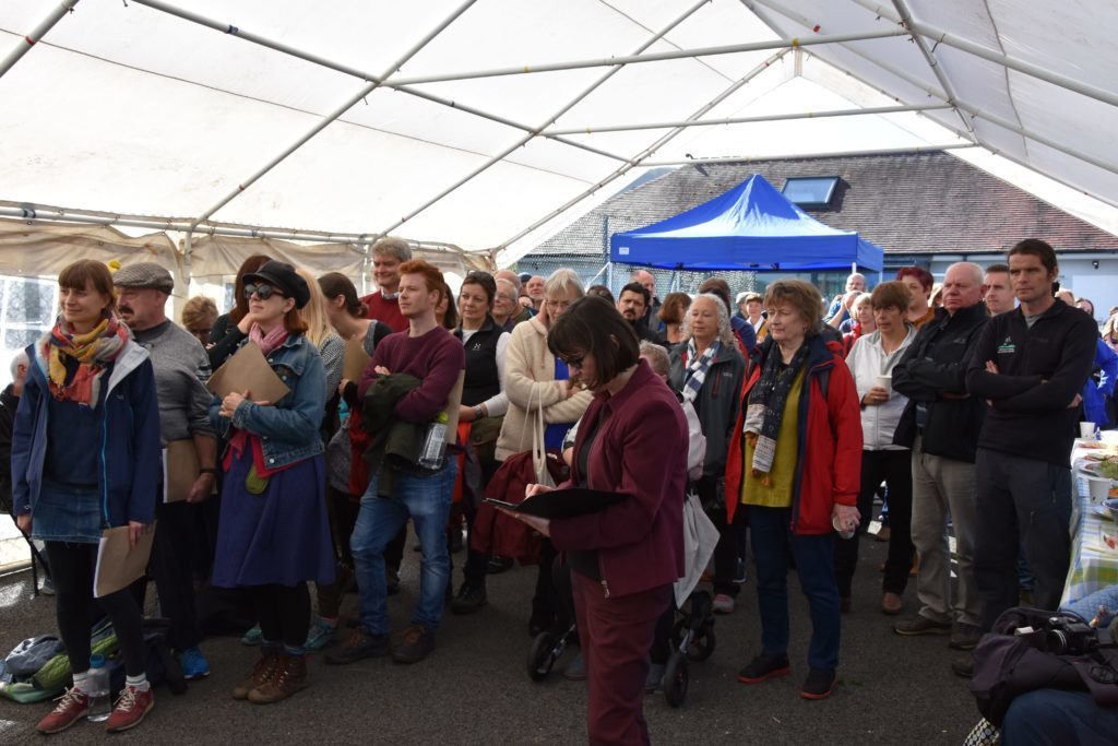 Attendees gather under the marquee to hear the speakers at the opening ceremony.