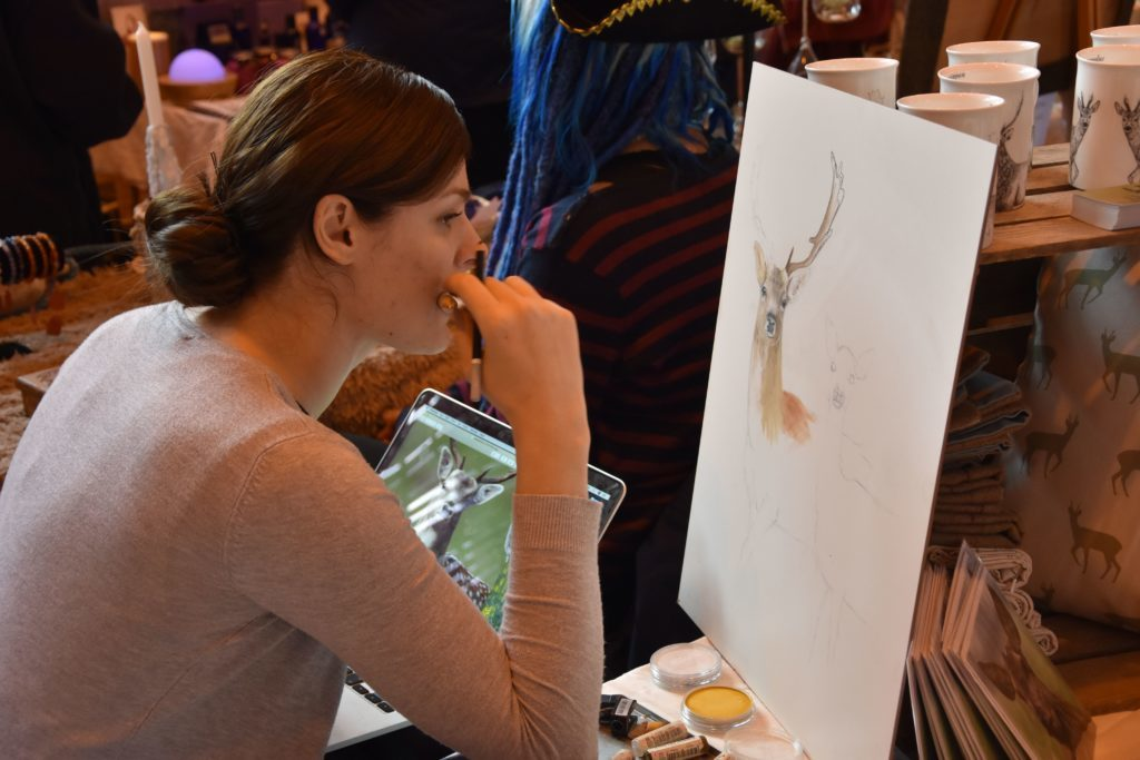 Sophie Littlewood of Déercor paints a picture of a stag at her deer themed home decor stall.