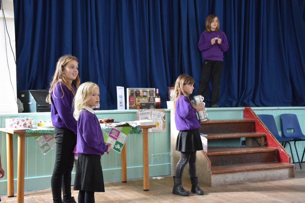Kilmory Primary pupils hold a raffle, call out the prize winners and deliver the prizes.