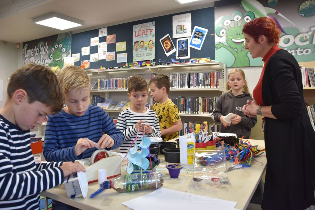 Library assistant Nickey Summer watches over children creating boats using craft materials.