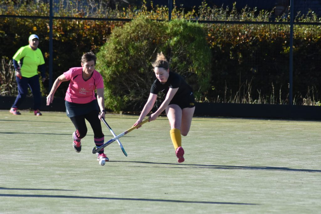 Arran's Lorraine Hewie challenges an Glasgow University player for the ball while umpire Pauline Reid keeps a close eye on the game.