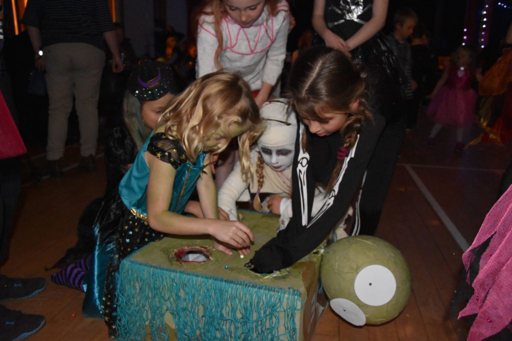 What's in the box, children reach into the mystery box to dig out Hallowe'en prizes.