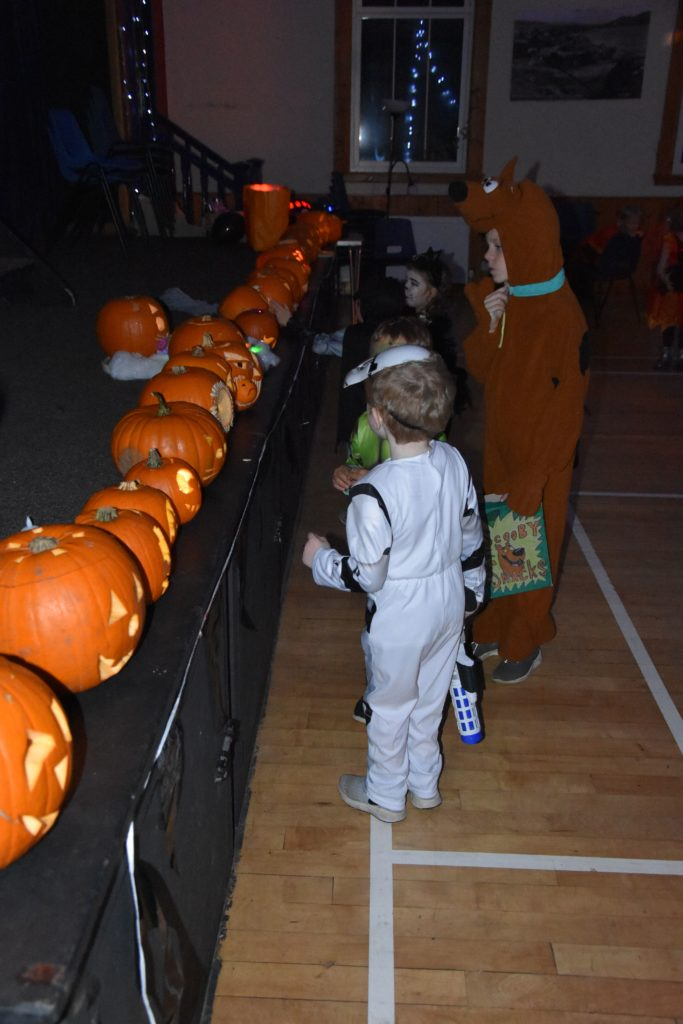 Children admire an impressive carved pumpkin display at Whiting Bay Hall.