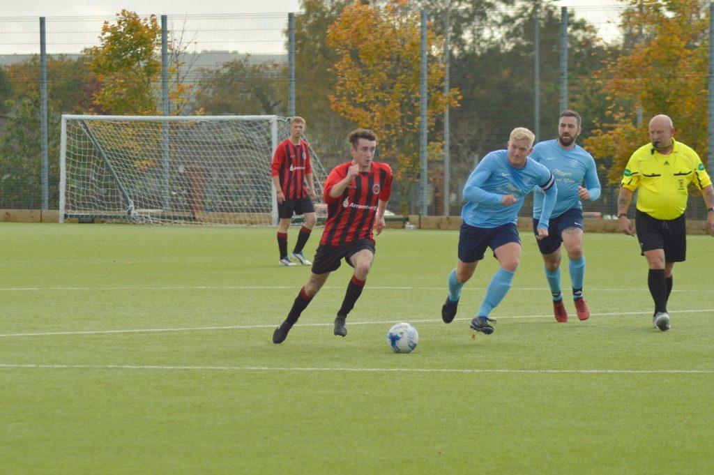 Glencairn players chase down Johnny Sloss in full stride.