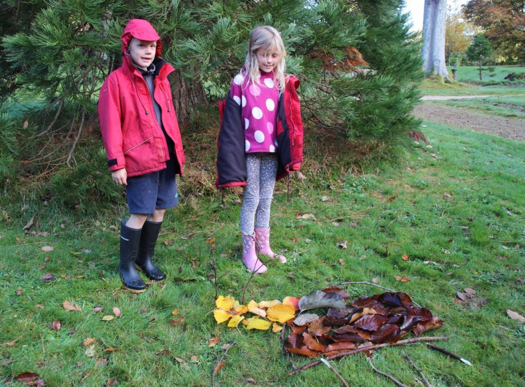 Two children admire their colourful creation using fallen leaves and sticks. Photograph: Kate Sampson.