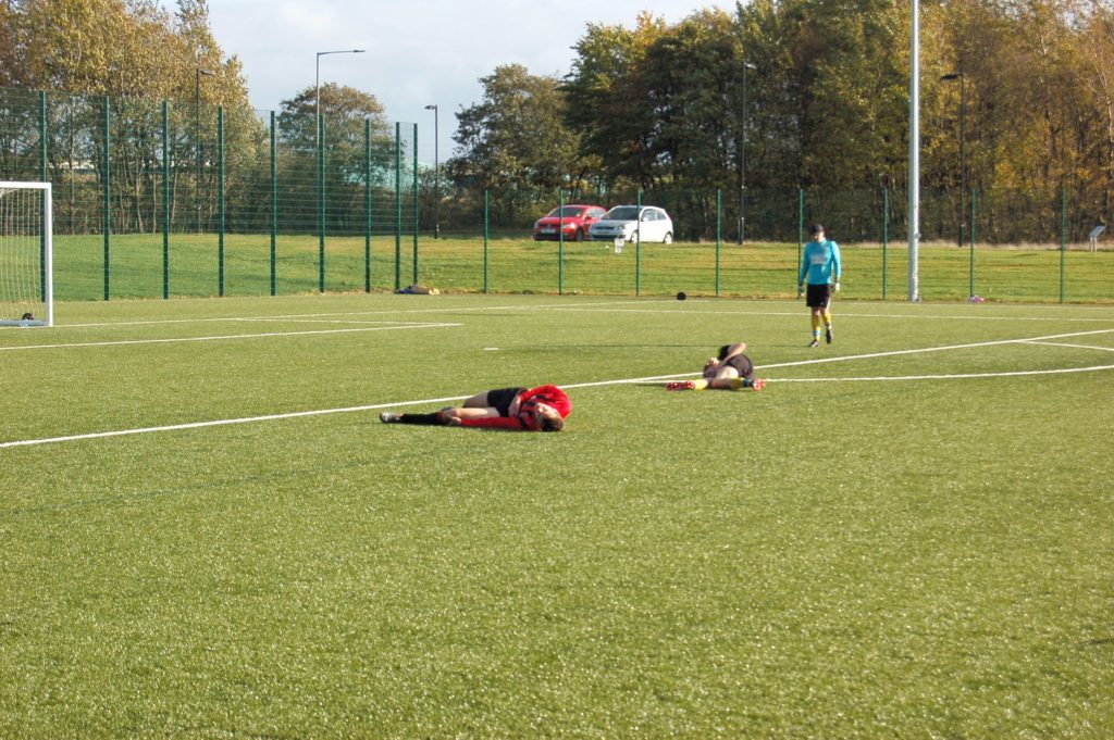 Players from each side take a few minutes of respite after a bruising but accidental encounter.