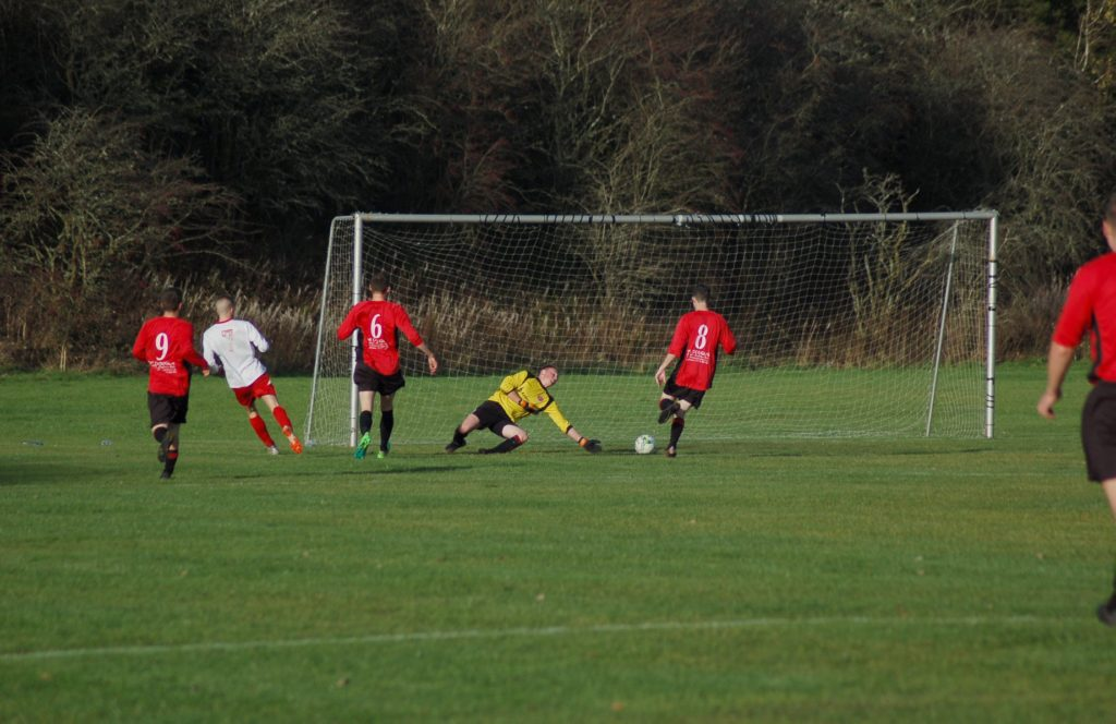 Arran goalkeeper Stephen Judge throws himself to the ground in an attempt to prevent a sideward attack at goal.